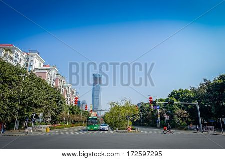 SHENZEN, CHINA - 29 JANUARY, 2017: Nan Shan neighborhood, inner city streets and sorroundings, beautiful mix of green trees combined with buildings, modern architecture, light traffic, totally blue skies.