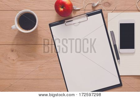 Writing, planning or preparing to exam background. Study and work in office mockup. Top view of note paper, pen, coffee, apple and mobile phone on wood with copy space