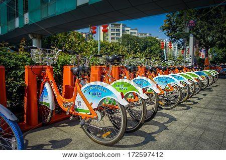 SHENZEN, CHINA - 29 JANUARY, 2017: City bike parking, row of orange bikes connected to automatic machines on city street.