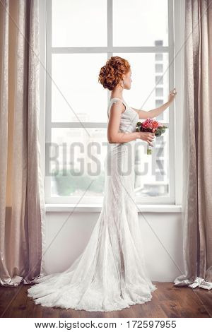 Wedding. Beautiful bride indoors with bouquet of flowers against big window in full lenght back side view