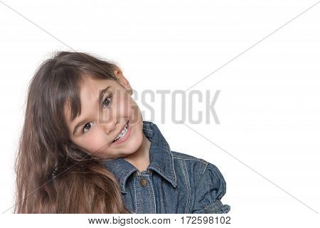 Portrait of long haired brunette little girl isolated on the white background. The girl has her head tilted and is looking at the camera.
