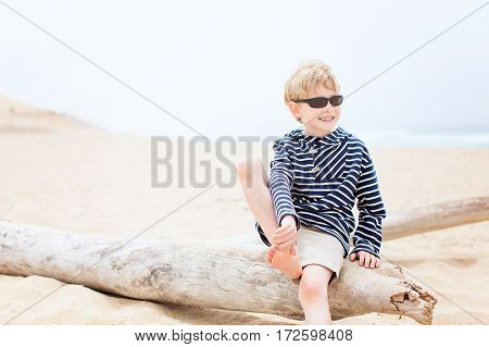 cute relaxed smiling boy in sunglasses enjoying time at the beach in california