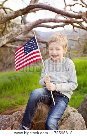 smiling caucasian boy holding american flag celebrating 4th of july independence day