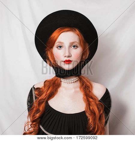 Red-haired girl with red lips with a black hat with long hair. Bright unusual appearance