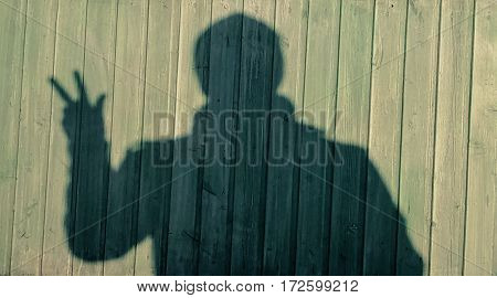 the shadow of a man against a green wooden wall gestures