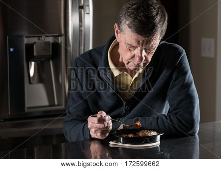 Lonely and depressed senior male sitting alone at kitchen table eating a microwaved ready meal of curry from plastic tray