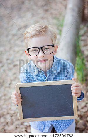 cute caucasian little boy in glasses holding empty blackboard sign back to school concept