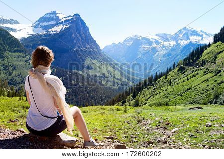 back view of young woman enjoying gorgeous mountain and valley view in glacier national park montana state usa