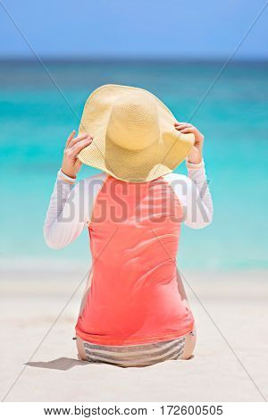 back view of young woman in rashguard and sunhat enjoying sunbathing at beautiful caribbean island sun protection and summer vacation concept