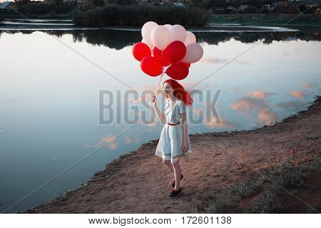 Red-haired girl with red and white balloons in nature against the sky. Happy woman. Fine art picture