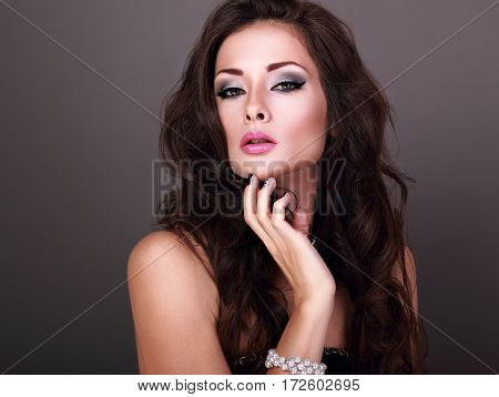 Beautiful Bright Evening Makeup Woman With Long Curly Hairstyle Looking Sexy In Pearl Bangle On Grey