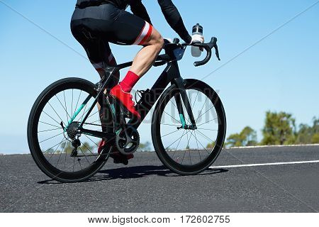 Men cycling road bike on the road with a bottle of drink in my hand,clear summer day