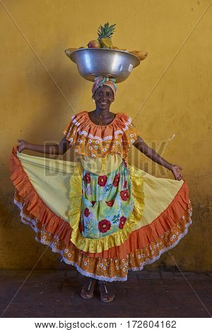 CARTAGENA DE INDIAS, COLOMBIA - JANUARY 24, 2017: Woman in traditional costume posing for a photograph whilst selling fresh fruit in the historic walled city of Cartagena de Indias in Colombia.