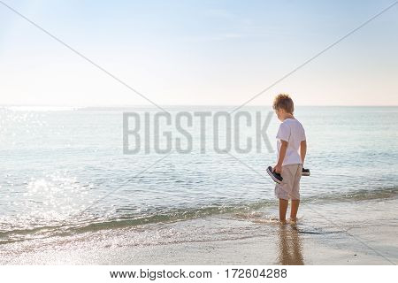 Adorable kid boy standing on the sandy beach by the ocean and looking on the gorgeous summer view. Miami summer vacations. Blue sky with clouds as a background. Child on amazing beach.