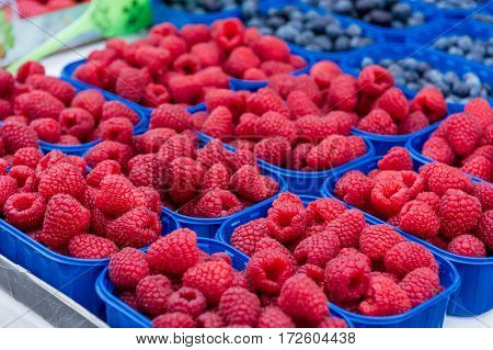 Rasberries and blueberries sold at store. Outdoor market.