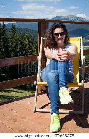 Girl is enjoying sunny day. Girl is sitting in deck chair on the veranda. Bukovel. Ukrainian Carpathians.