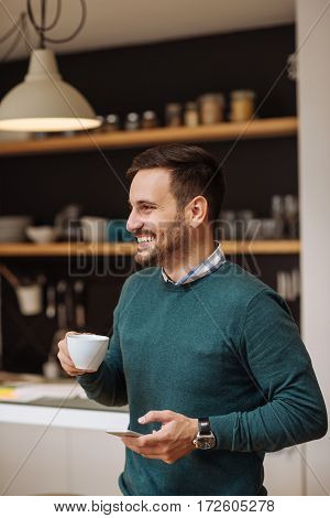 Young casual businessman enjoying a coffee break at home.