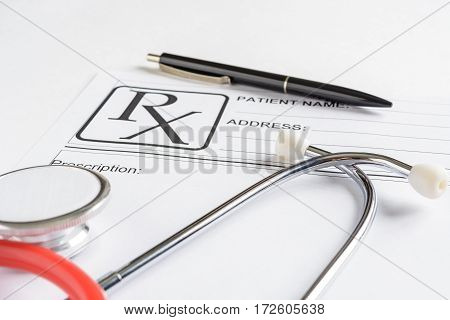 Medical prescription form with stethoscope and pen over it