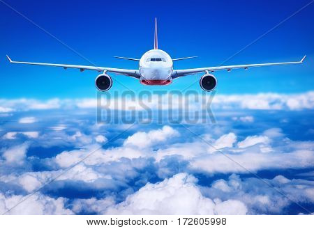 passenger airliner flying above the clouds in the blue sky
