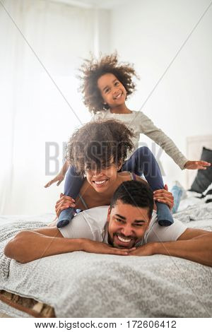 Happy african american family playing in bed.