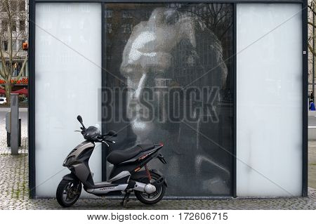 FRANKFURT, GERMANY - FEBRUARY 19: A small wheel motorcycle or scooter stands in front of a Goethe picture on the horse market on February 19, 2014 in Frankfurt.