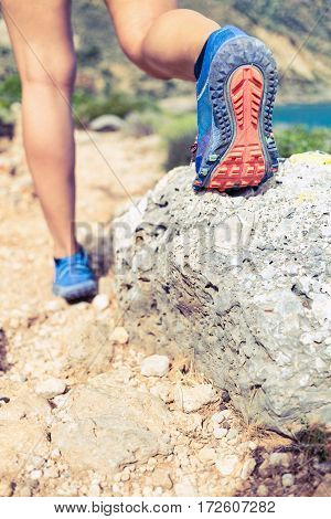 Hiking or running woman in beautiful mountains inspirational landscape. Sole of sports shoe and legs of person on rocky footpath. Hiker trekking or walking of footpath. Healthy fitness lifestyle outdoors concept.