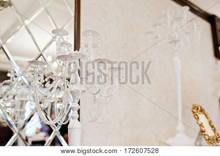 White Candlestick Against Mirror At Wedding Reception.
