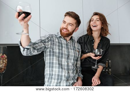 Photo of young smiling loving couple standing in kitchen at home indoors. Drinking alcohol.