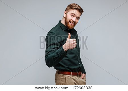 Smiling Bearded man in shirt showing thumb up and looking at camera. Isolated gray background