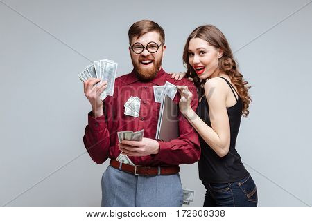 Cunning Woman stick to Male nerd with money. Isolated gray background