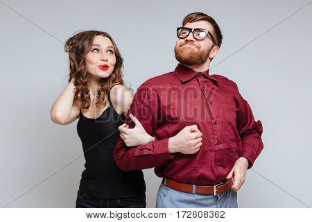 Pretty Woman which holding hand of Funny Bearded Male nerd in eyeglasses and funny clothes
