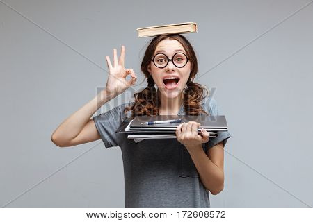 Funny Female nerd in eyeglasses with book on head which holding laptop and notebook in hand and showing ok sign