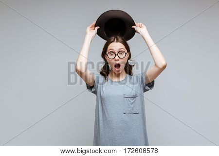 Shocked Female nerd holding overhead her hat with open mouth and looking at camera