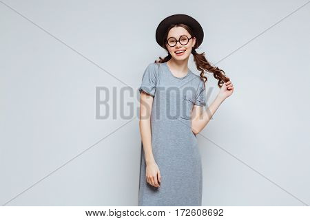 Female nerd in black hat and eyeglasses which holding her hair and looking at camera