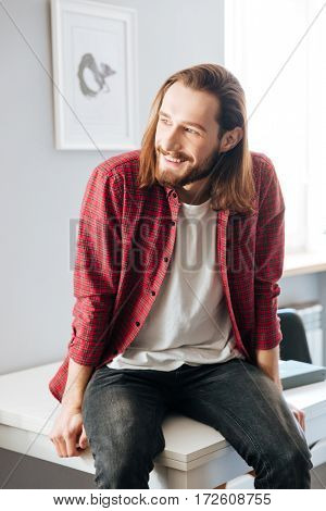 Happy attractive young man in plaid shirt sitting on the table at home