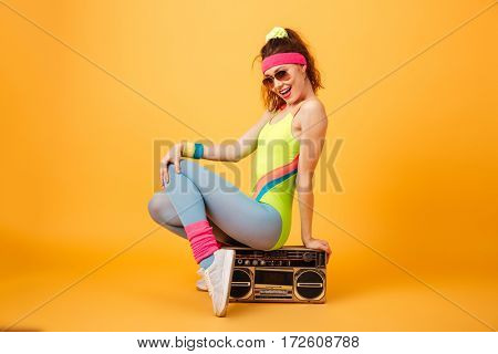 Smiling cute young sportswoman in sunglasses sitting on retro boombox over yellow background