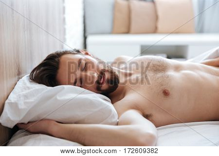 Attractive bearded young man sleeping in bed at home