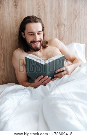 Cheerful attractive young man lying and reading book in bed