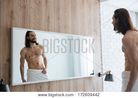 Cheerful naked bearded young man with towel looking at the mirror at home