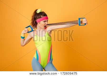 Strong young woman athlete shouting and exercising with expander over yellow background