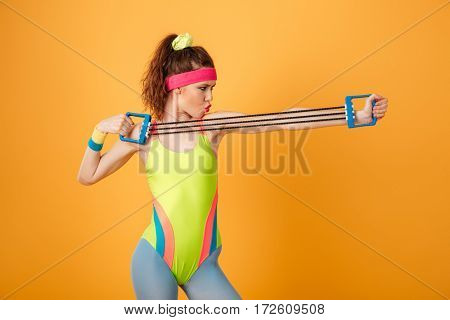 Serious focused young fitness woman standing and training with expander over yellow background