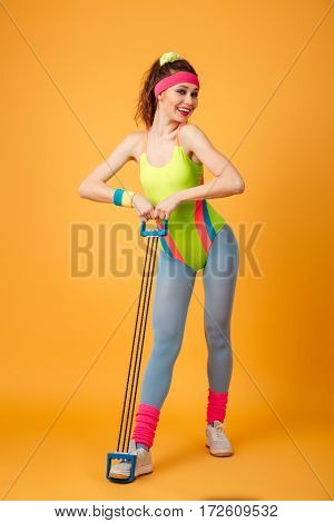 Cheerful beautiful young woman athlete standing and working out with expander over yellow background
