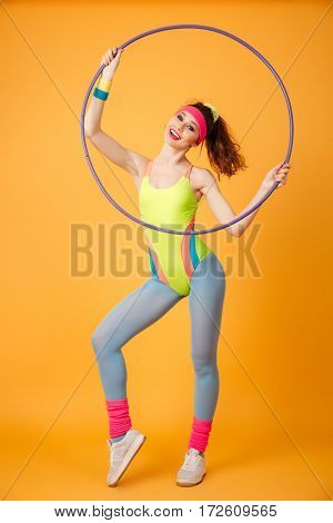 Happy young woman athlete standing and looking through hula hoop over yellow background