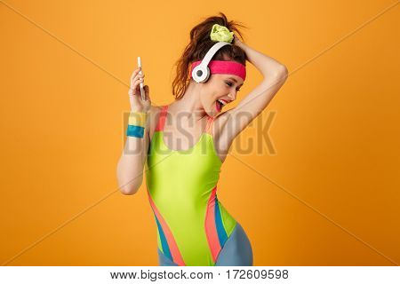Happy young woman athlete listening to music from smartphone and dancing over yellow background