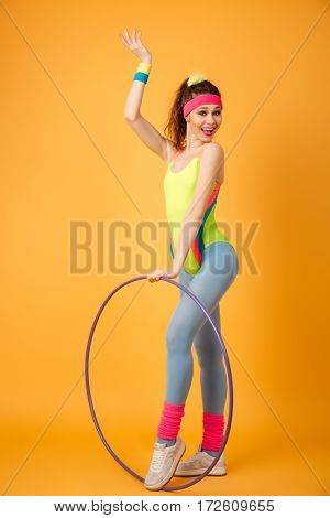 Happy young woman athlete with hula hoop holding copyspace on palm over yellow background