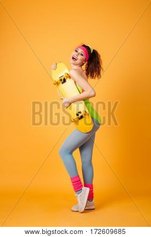 Full length of happy young sportswoman standing and holding yellow skateboard over yellow background