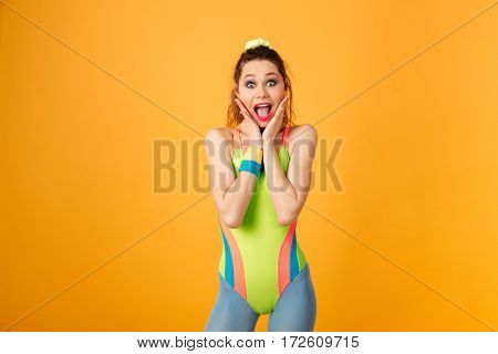 Surprised pretty young fitness woman standing and shouting over yellow background