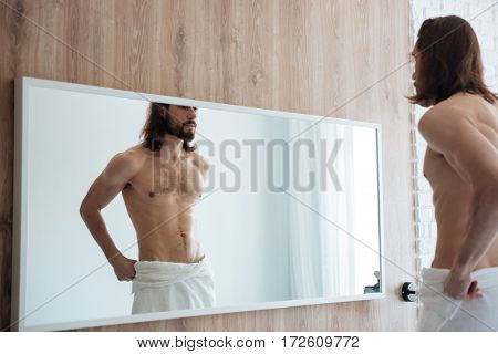Attractive bearded young man with towel standing and looking at the mirror