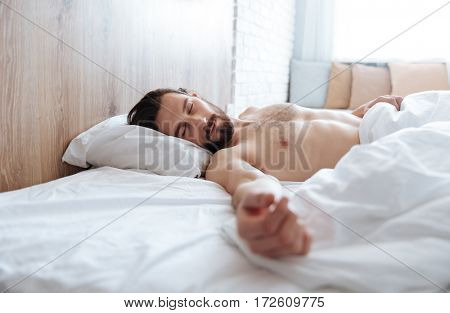 Tired fatigued young man lying and sleeping in bed at home