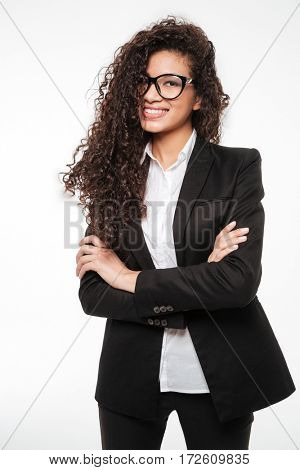 Photo of incredible african business lady wearing glasses standing over white background. Looking at camera.